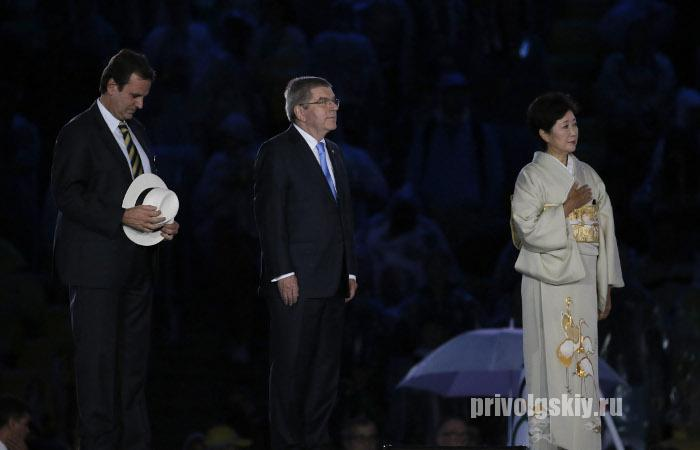epa05506286 Rio Mayor Eduardo Paes (L), IOC President Thomas Bach (C) and Tokyo governor Yuriko Koike hand over the Olympic flag during the Closing Ceremony of the Rio 2016 Olympic Games at the Maracana Stadium in Rio de Janeiro, Brazil, 21 August 2016.  EPA/SERGEI ILNITSKY