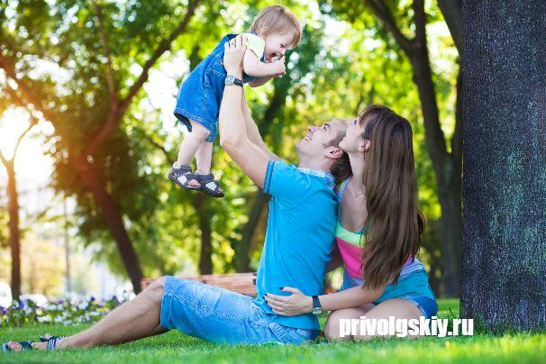 happy parents with a baby in a beautiful summer park